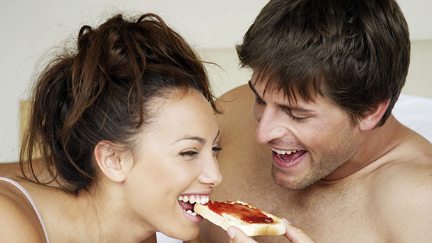 Couple eating in bed