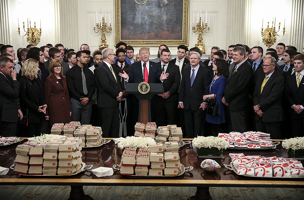 President Donald Trump speaks behind a table full of McDonald's hamburgers, Chick fil-a sandwiches and some other fast food as he welcomes the 2018 Division I FCS National Champions: The North Dakota State Bison in the State Dining Room of the White House on March 4, 2019 in Washington, DC. (Photo by Oliver Contreras/SIPA USA)(Sipa via AP Images)